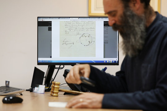 Meron Eren of Kedem Auction House sits in his office as a scan of a letter handwritten by composer Richard Wagner in 1869 is seen on his computer screen, ahead of an auction in Jerusalem