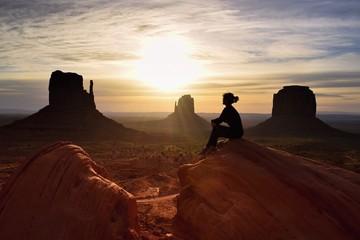 Mounument Valley, silhouette of woman hiker, watching a beautiful american desert landscape
