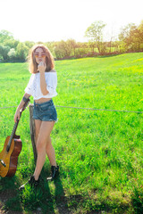 alternative summer vacation concept for pretty young brunette model girl playing guitar on a sunny day. sun backlight and girl immersed in her music. lifestyle of the singer artist