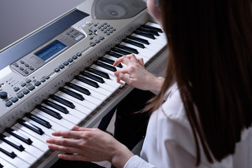 cropped portrait of a young brunette in front of the synthesizer, practiced in the game of keys