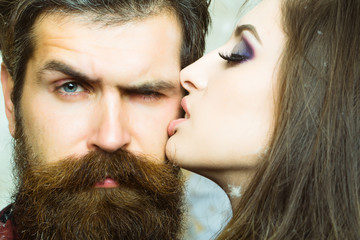 Woman kiss hipster with long beard, love. Sensual woman with makeup skin and bearded man. Couple in love and family concept. Beauty salon and barber shop. Skincare and hair care concept