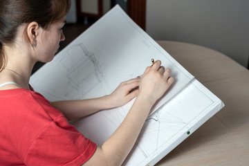 Student architect prepares a draft work, draws a pencil on a white tablet