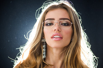 Optics store concept. Beauty fashion girl with makeup and big earrings jewelry, dark studio background. Woman with sensual lips wears metallic eyeglasses for vision. Girl needs modern eyeglasses.