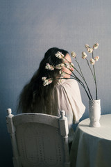 woman sitting near table with flowers