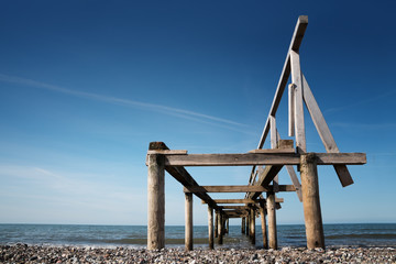Broken wooden pier or jetty leads into the sea against a blue sky, perspective from below, copy space