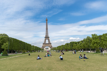 Paris, France - circa May, 2017: Lots of people relaxing and having fun on Champ de Mars with the Eiffel Tower on background on a sunny day