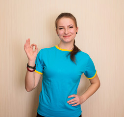 Portrait of a cheerful teen girl showing okay gesture.