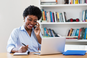 African american businesswoman with computer at phone