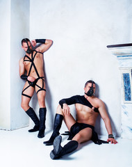 two muscular striptease dancers wearing leather