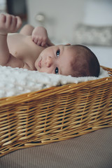 Newborn baby girl lying in a wicker basket on the bed