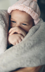 Portrait of newborn baby girl with wool cap wrapped in a blanket