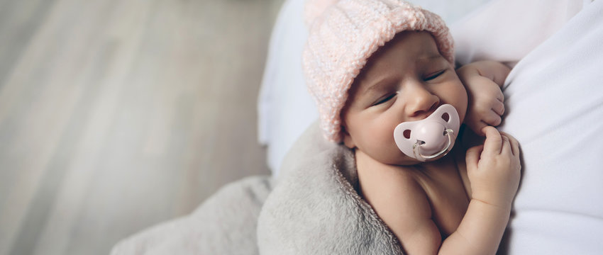Closeup of face of baby girl with pacifier sleeping