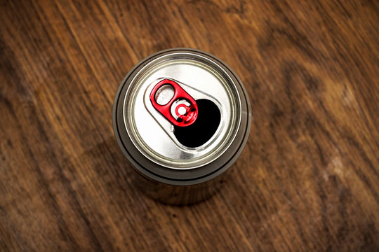 Tin can with beer on the background of wood texture