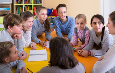Nice woman teacher and children sitting at table