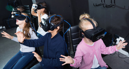 Enthusiastic children in virtual reality glasses in quest room