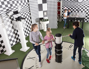 kids look for a way out in quest room in chess style