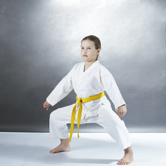 On a gray background a girl in karategi stands in a karate rack