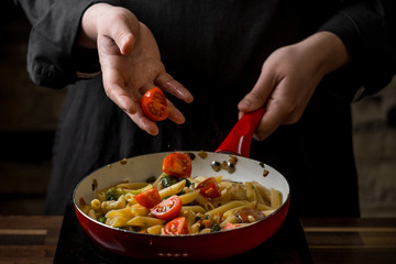 Close-up of a chef preparing an Italian penne pasta on a red frying pan close-up. The concept of flying products.