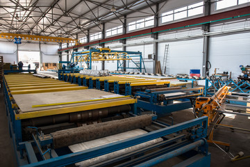 Thermal insulation sandwich panel production line for construction. Manufacturing storage with machine tools, roller conveyor