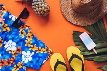 Top view of Summer accessories on orange background