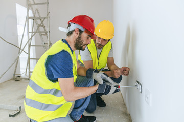 Worker explaining to another how to place plugs.