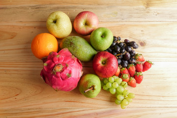 Set of different fruits on wooden table.