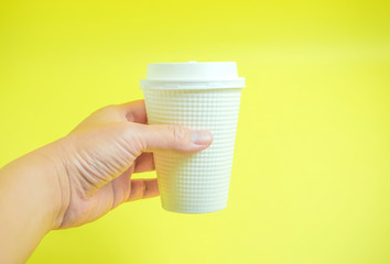 The photograph which catches a drink for takeout.  テイクアウト用のドリンクをつかんでいる写真、紙コップをつかんでいる写真 黄色背景