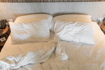 rumpled bed with white messy pillow