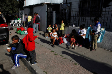 Central American migrants, moving in a caravan through Mexico and traveling to request asylum in the U.S., eat outside the Juventus 2000 shelter after arriving to Tijuana