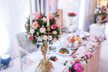 White candles on metal gold chandelier stand on tables at luxury wedding reception in restaurant. stylish decor and adorning