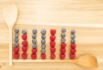 Statistical graph made of kitchen spoons, fresh blueberries and raspberries on a brown wooden cutting board