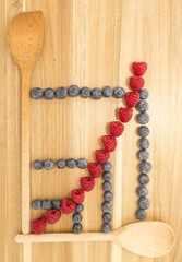 Statistical line curve graph made of kitchen spoons, fresh blueberries and raspberries on a brown wooden cutting board