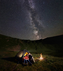Embracing young pair backpackers having a rest in illuminated tent by the campfire at night camping, enjoying the incredible starry sky with bright Milky way. On background of mountains and lake