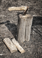 The old rusty ax sticks out in the log during the firewood splitting.
