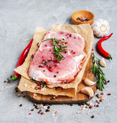 Fresh raw pork chops with spices and herbs