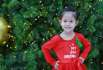 Cute little Asian girl in red dress with smiling and looking at camera on pine tree background.