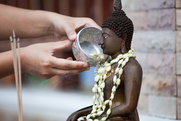 Woman hand hold little bowl to bath Buddha statue for blessing ceremony celebrate Songkran in new year water festival, Thai culture concept.