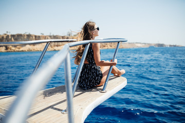 young beautiful woman lying on the deck of a yacht at sea.