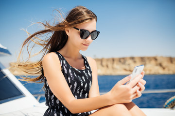Young woman travel with smartphone on yacht. Chatting on smartphone on yacht.
