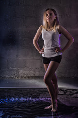Portrain of the girl in the white shirt with water drop in a dark room illuminated by light during a photoshoot with water