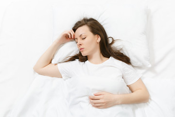 Top view of happy calm brunette young woman lying in bed with white sheet, pillow, blanket. Sleeping pretty female spending time in room. Rest, relax good mood concept. Copy space for advertisement.