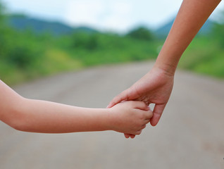 Close up of Sister hold hands with small children walking on the road.