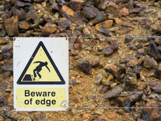 Warning sign at the edge of unstable cliff