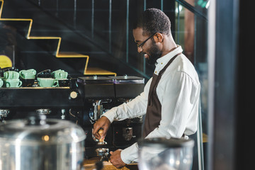 side view of smiling african american barista in apron and eyeglasses making coffee at coffee machine
