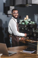 cheerful young african american barista in eyeglasses smiling at camera while making coffee at coffee machine