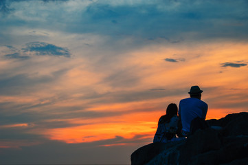 Silhouette of a loving couple sitting on a rock over evening tropical sea, over blurred background. Sunset pastel background with light fair.