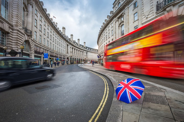 London, England - Iconic red double-decker bus and black taxi on the move on Regent Street with british umbrella