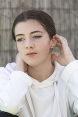 Portrait of a teenager without looking at camera. Vertical shot with natural light.
