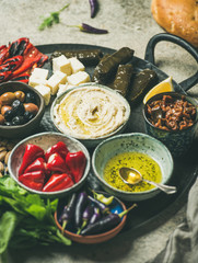 Mediterranean, Middle Eastern meze starter platter. Stuffed pickled paprikas, dolma, hummus, spiced oil, olives, sundried tomatoes, nuts, cheese, flatbread on tray selective focus close-up