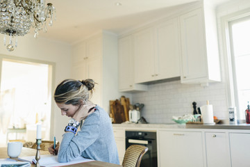 Woman sitting and writing in kitchen